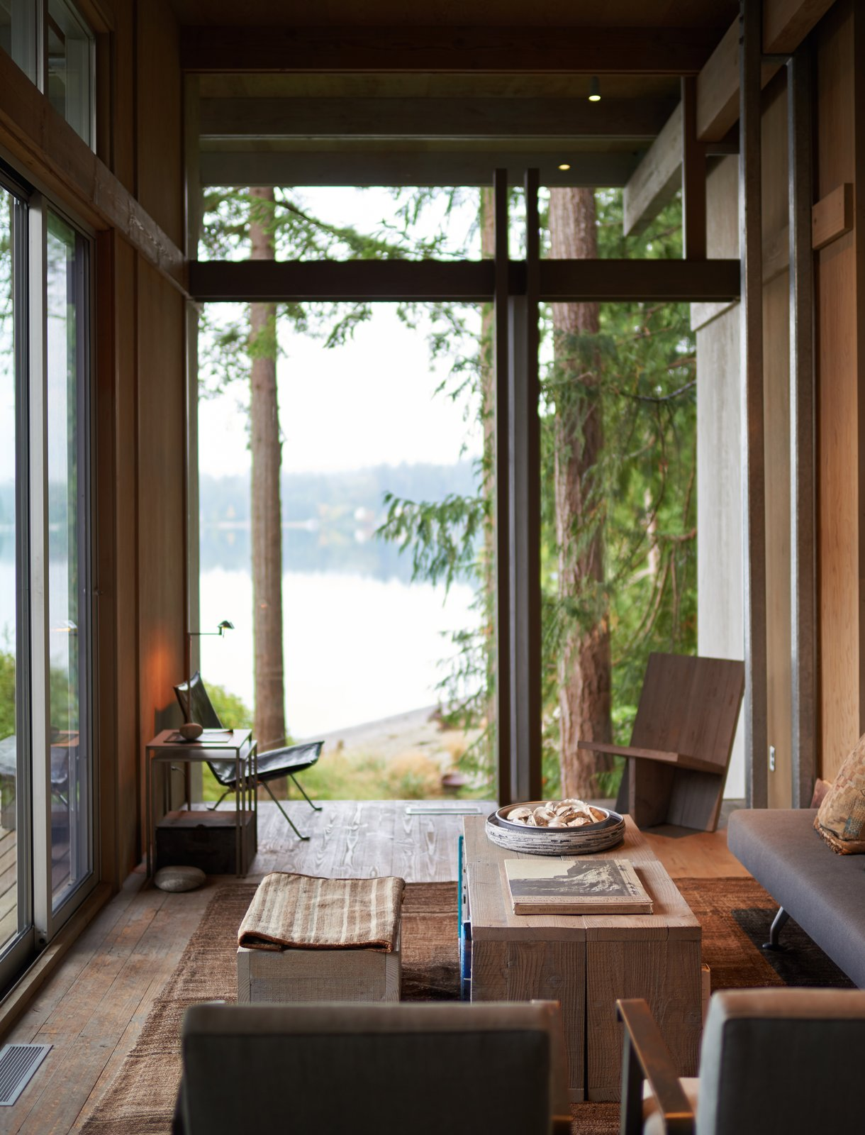 the-living-rooms-large-wall-of-glass-frames-a-view-of-the-adjoining-grassy-field-and-puget-sound-visually-blending-indoors-and-outdoors.jpg