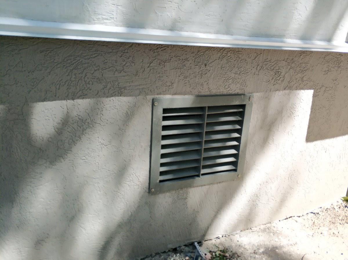 Решетка системы естественной вентиляции в цоколе дома